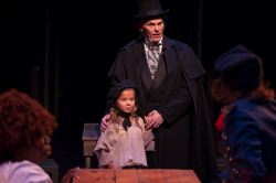 Jean Valjean (Daniel Felton) pays the Thenardiers to take young Cosette (Ella Boodin) to raise her in a warm and loving home